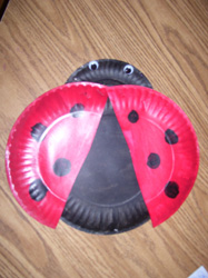 For this project you will need one small and two large paper plates. Cut the small paper plate in half. Discard one half and paint the other half black. & Ladybug Paper Plate Project F